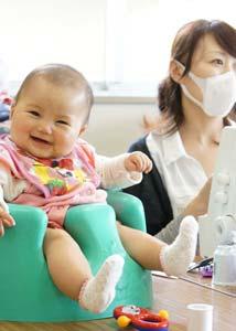 働くママの傍らで笑顔の赤ちゃんの写真。