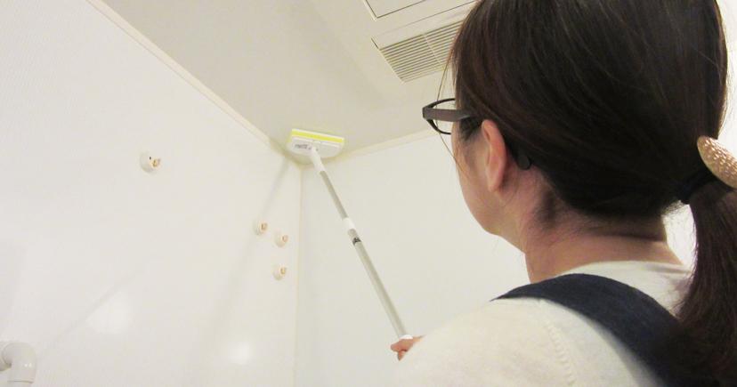 柄つきのスポンジで天井にカビ取り剤を塗っている