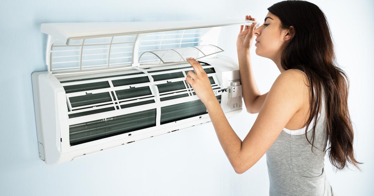 エアコンの中を開けてフィルターをチェックしている女性