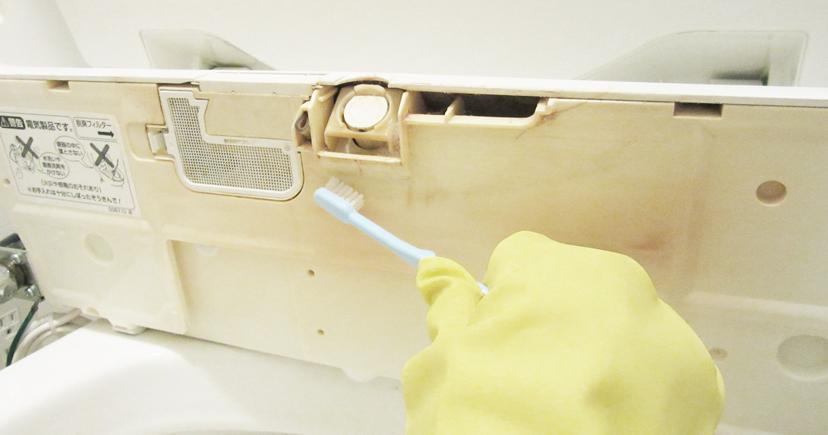 歯ブラシで洗浄便座をこすり洗いする
