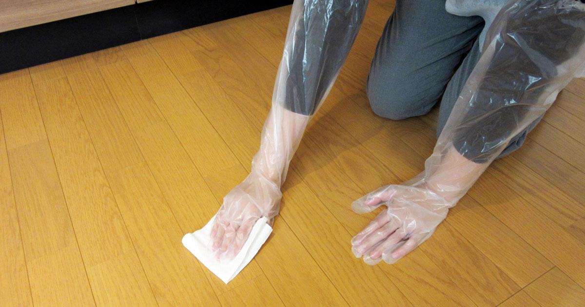 キッチンペーパーでフローリングを拭き取る女性