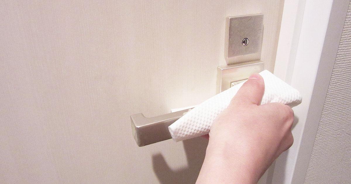ドアノブを拭き掃除する手の写真