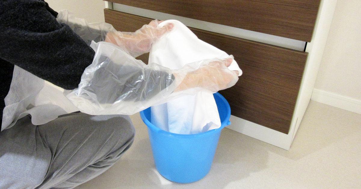 水が入ったバケツに衣類を入れる