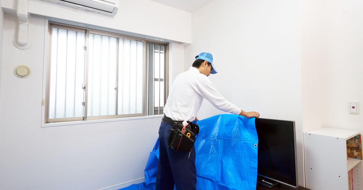 家具と床を養生するスタッフ
