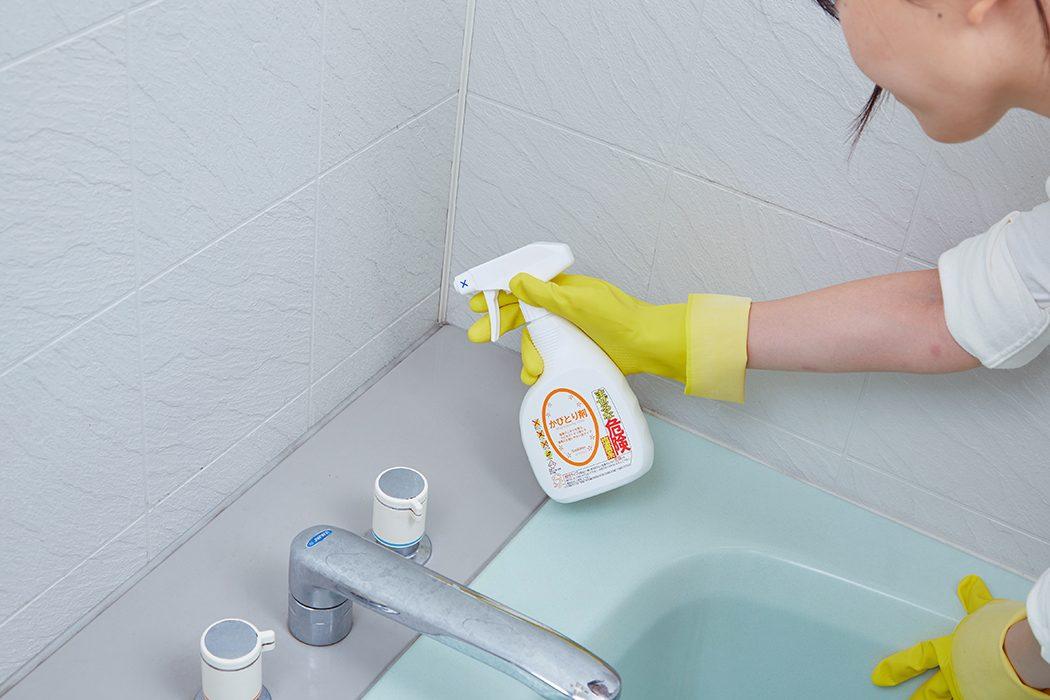 かびとり剤を浴室のコーナーに吹き付ける女性の写真