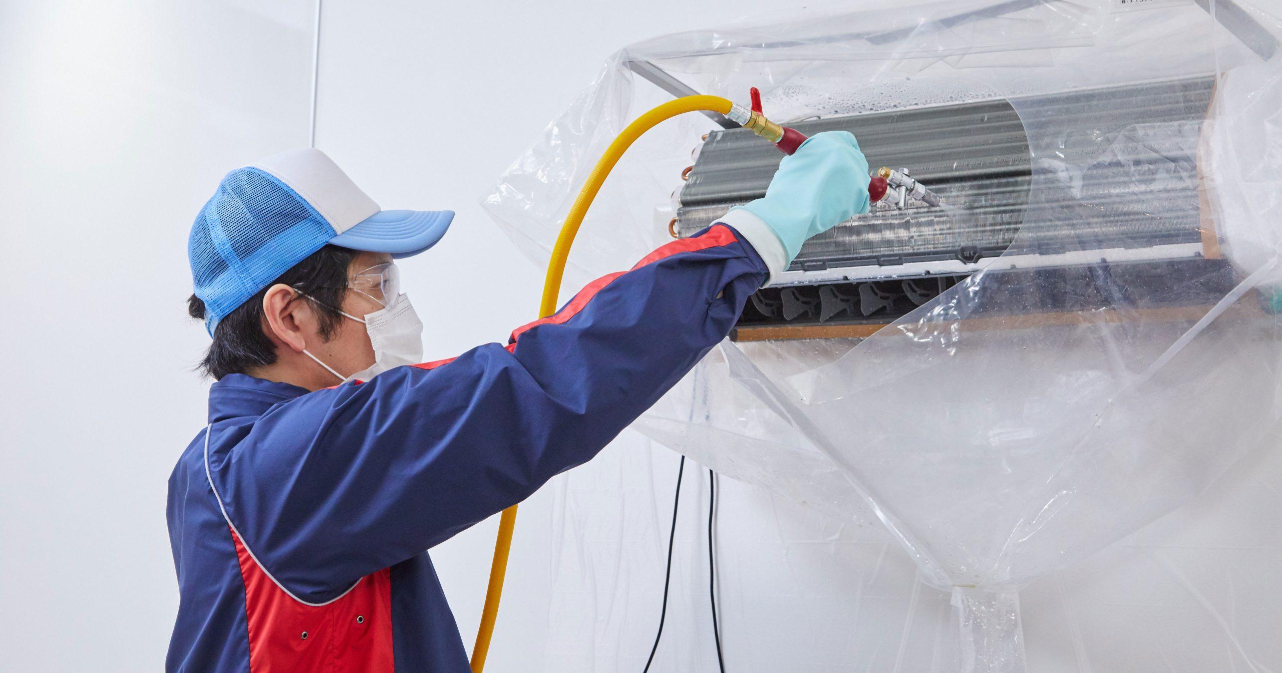 プロがエアコンを高圧洗浄している写真