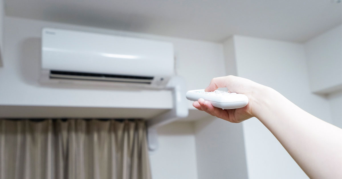エアコンをつける手の写真