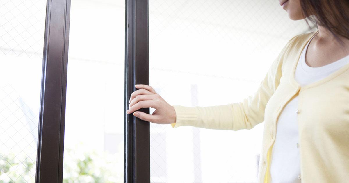 窓を開ける女性の写真