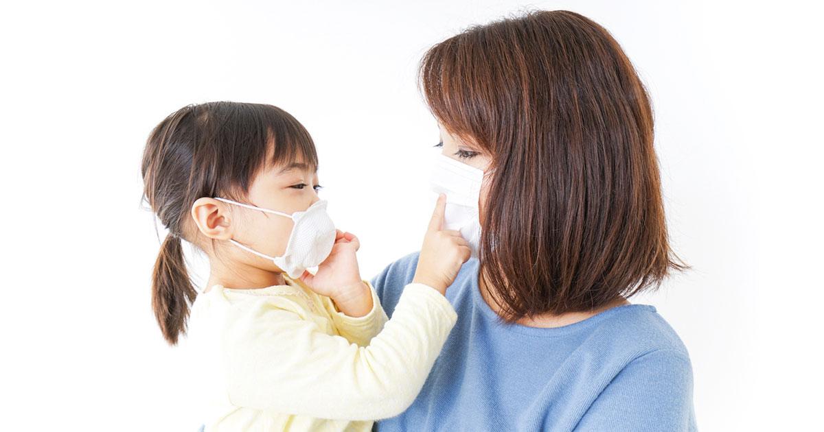 マスクをつけて向き合う親子の写真