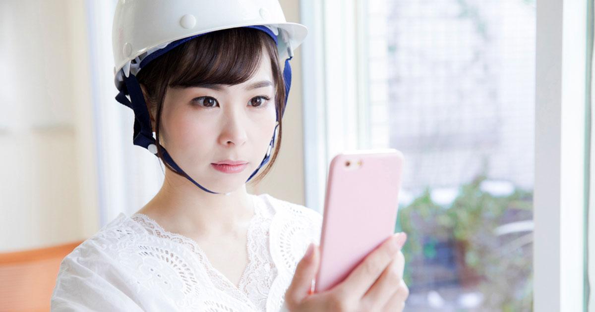 スマホを見ているヘルメットをかぶった女性の写真